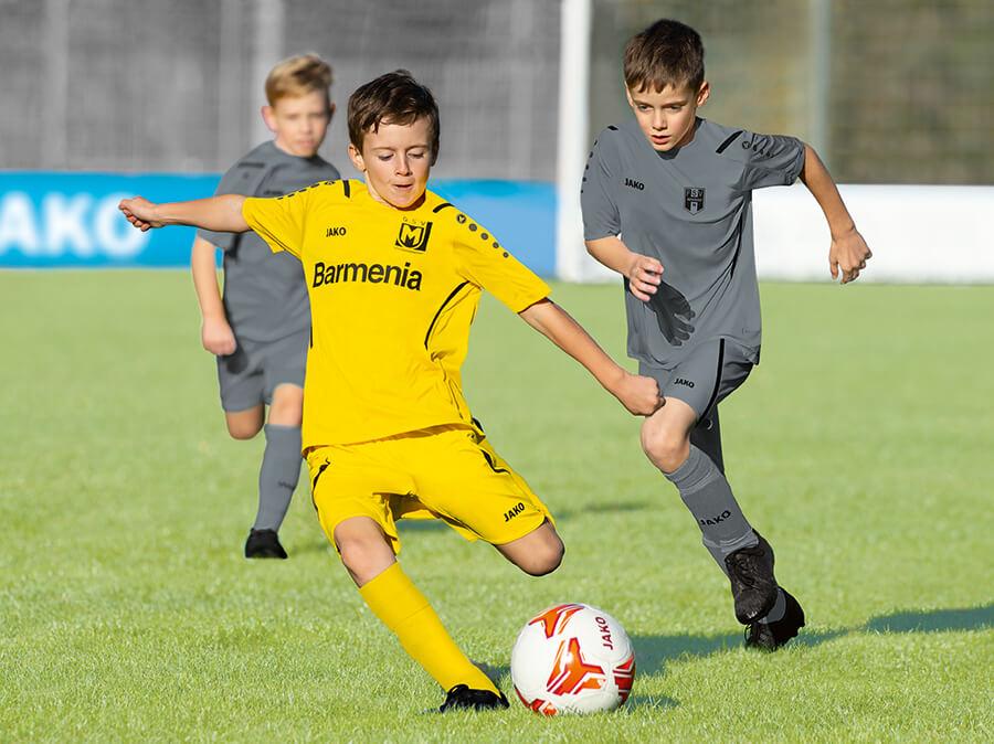 Kinderen voetballen in JAKO-truien