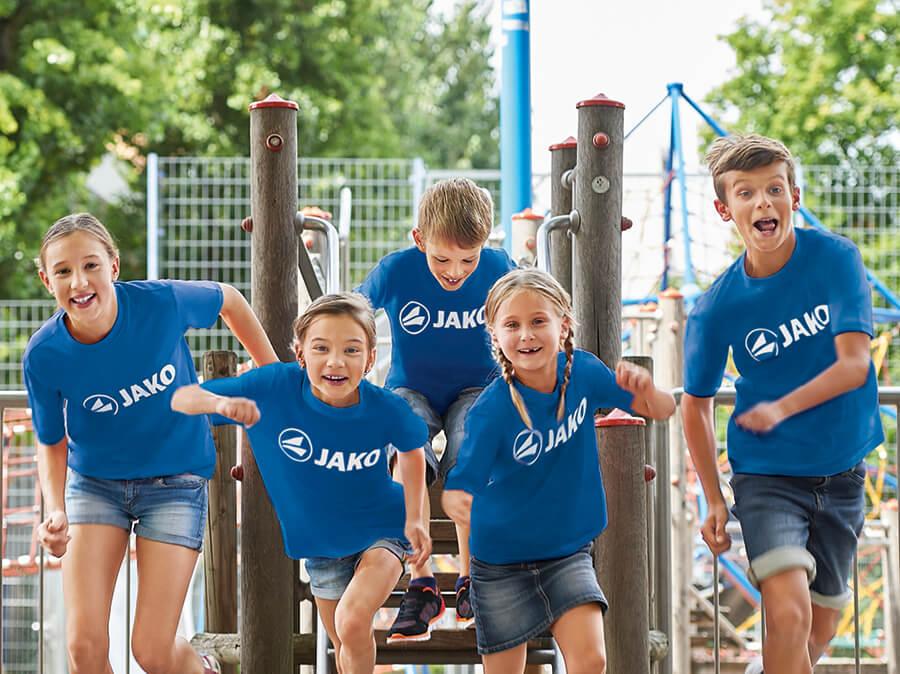 Een groep kinderen met JAKO T-shirts speelt in de speeltuin.